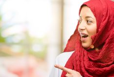 Young arabian woman wearing hijab  over natural background. Young arab woman wearing hijab pointing away side with finger Stock Image