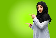 Young arab woman wearing hijab isolated over green background. Young arab woman wearing hijab pointing away side with finger Stock Photography