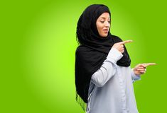 Young arab woman wearing hijab isolated over green background. Young arab woman wearing hijab pointing away side with finger Stock Photos