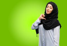 Young arab woman wearing hijab isolated over green background. Young arab woman wearing hijab proud, excited and arrogant, pointing with victory face Royalty Free Stock Photos
