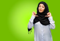 Young arab woman wearing hijab isolated over green background. Young arab woman wearing hijab proud, excited and arrogant, pointing with victory face Stock Photo