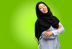 Young arab woman wearing hijab isolated over green background stock photo