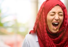 Young arabian woman wearing hijab isolated over natural background. Young arab woman wearing hijab stressful, terrified in panic, shouting exasperated and Royalty Free Stock Photos