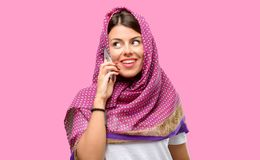 Young arab woman. Wearing hijab happy talking using a smartphone mobile phone Royalty Free Stock Photos