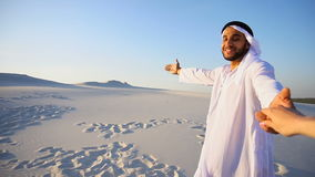 Young Arabian guide guides girl`s hand and conducts conversation, walks wide desert on warm summer evening. Cute Muslim young man and tourist guide with smile stock video
