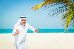 Young Arabian Man On The Beach. Young arabian man standing on the beach, giving you a thumbs up Stock Photo