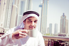 Young Arabian Man Having Coffee. Young arabian man having a cup of coffee at dubai marina Stock Photography