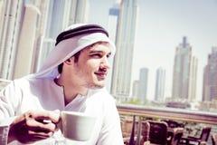 Young Arabian Man Having Coffee. Young arabian man having a cup of coffee at dubai marina Stock Photos