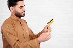 Young Arabian man keeps bitcoin and golden credit card on the white background. He wear interesting arabian wear with an accurate pattern. A man looks very Royalty Free Stock Photos