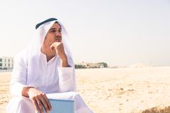 Young Arabian Man Sitting At The Beach Stock Photo