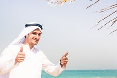 Young Arabian Man On The Beach. Young arabian man standing on the beach, giving you a thumbs up Royalty Free Stock Photo