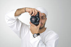 Young Arabian man using holding his camera ready to shoot, isolated Royalty Free Stock Photography