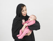 Young Arabian mother holding her little baby. Isolated on white Royalty Free Stock Photo
