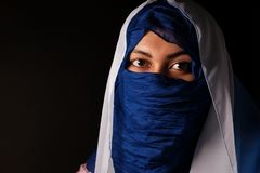 Young arabian muslim woman in blue and whitel hijab isolcated on black. Royalty Free Stock Images
