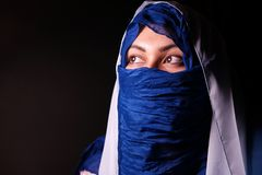 Young arabian muslim woman in blue and whitel hijab isolcated on black. Stock Photography