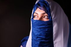 Young arabian muslim woman in blue and whitel hijab isolcated on black. Royalty Free Stock Image