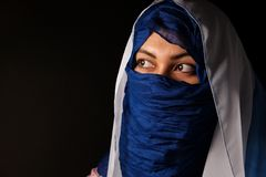 Young arabian muslim woman in blue and whitel hijab isolcated on black. Stock Images