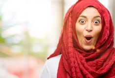 Young arabian woman wearing hijab isolated over natural background. Young arab woman wearing hijab happy and surprised cheering expressing wow gesture Stock Photos