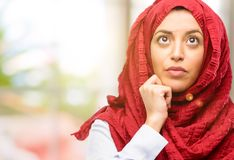 Young arabian woman wearing hijab isolated over natural background. Young arab woman wearing hijab thinking and looking up expressing doubt and wonder Royalty Free Stock Images