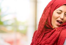 Young arabian woman wearing hijab isolated over natural background. Young arab woman wearing hijab blinking eyes with happy gesture Royalty Free Stock Images