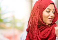 Young arabian woman wearing hijab isolated over natural background. Young arab woman wearing hijab pointing away side with his finger Stock Images