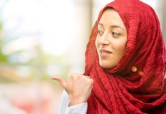 Young arabian woman wearing hijab isolated over natural background. Young arab woman wearing hijab pointing away side with his finger Royalty Free Stock Photography
