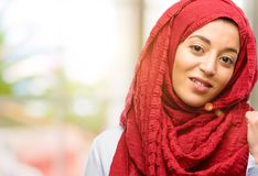 Young arabian woman wearing hijab isolated over natural background. Young arab woman wearing hijab pointing away side with his finger Stock Photos