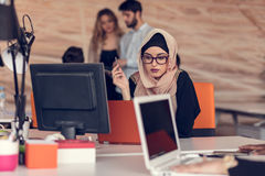 Young Arabic business woman wearing hijab,working in her startup office. Young Arabic business women wearing hijab,working in her startup office Stock Photo