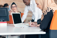 Young Arabic business woman wearing hijab,working in her startup office. Young Arabic business women wearing hijab,working in her startup office Royalty Free Stock Images