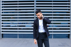 Young arabic man shows neck pain tired in business center Royalty Free Stock Photo