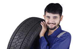 Young Arabic mechanic carrying a tire. Portrait of a young middle eastern mechanic carrying a tire while smiling at the camera in the studio Royalty Free Stock Image