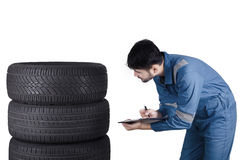 Young Arabic mechanic checks the tires Royalty Free Stock Photos