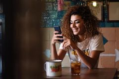 Arabic smiling woman in a beautiful bar looking at her smartphon Stock Image