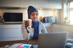 Young Arabic woman drinking coffee and working online at home stock photo