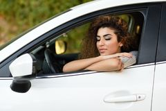 Young arabic woman inside a white car with eyes closed Royalty Free Stock Photos