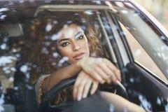 Young arabic woman inside a white car looking through the window. Beautiful young arabic woman inside a nice white car looking through the window. Arab girl Stock Image