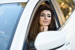 Young arabic woman inside a white car looking through the window. Beautiful young arabic woman ine a nice white car looking through the window. Arab girl wearing Royalty Free Stock Photo