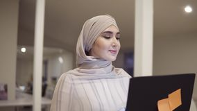 Young arabic woman wearing a hijab going by the hall while holding her black laptop in hands. Employee, working place. Conference hall, corridor. Low angle stock video footage