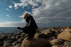 Young archaeologist on a boulder beach looking for exotic rocks on a coastline of a Baltic Sea. Cloudy weather stock photography