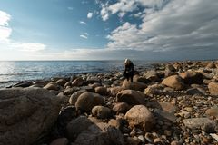 Young archaeologist on a boulder beach looking for exotic rocks on a coastline of a Baltic Sea. Cloudy weather royalty free stock photography