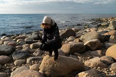 Young archaeologist on a boulder beach looking for exotic rocks on a coastline of a Baltic Sea stock photos