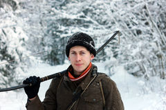 Young archer in winter snow forest. Young archer with bow and arrows hunting in the  winter snow northern forest Stock Image