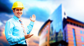 Young architect. Wearing a protective helmet standing on the building background Stock Photo