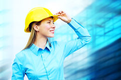 Young architect. Wearing a protective helmet standing on the building background Stock Photos
