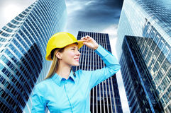 Young architect. Wearing a protective helmet standing on the building background Royalty Free Stock Photos