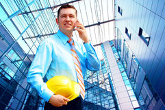 Young architect. Wearing a protective helmet standing on the building background Stock Photography