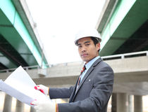 Young architect   with blueprint. Young architect  with blueprint on highway construction site Stock Photography