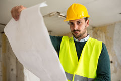 Young architect checking blueprint of building reconstruction stock image