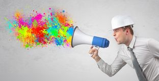 Young architect yelling with megaphone and colorful splash concept stock photos