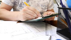 Young Architect or Designer Works on Project of House or Apartment. Pencil, ruler, marker and other stationery on the table stock video footage